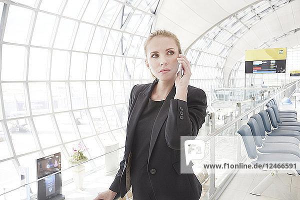Businesswoman working on phone at Suvarnabhumi Airport  Bangkok