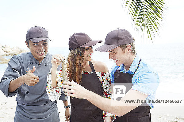 People wearing hats holding lobster on beach