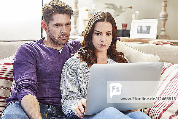 Mid adult married couple using laptop together.