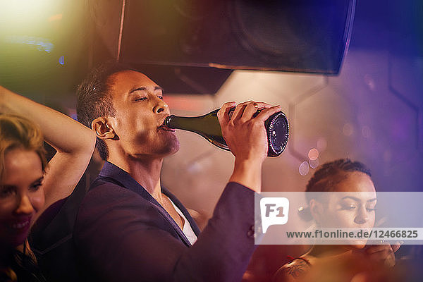 Young man drinking from champagne bottle at nightclub
