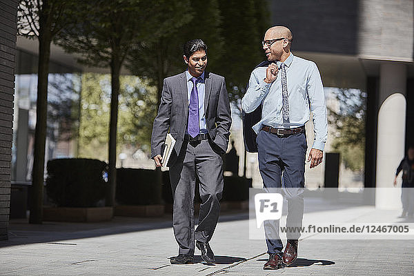 Businessmen walking along sidewalk together
