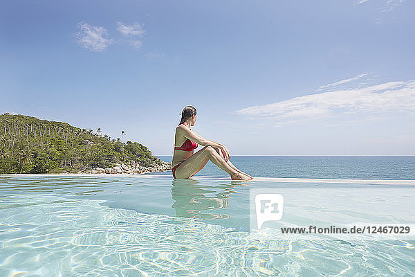 Young woman sitting on side of swimming pool