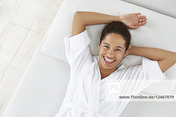 Woman lying down with hands above head  smiling.