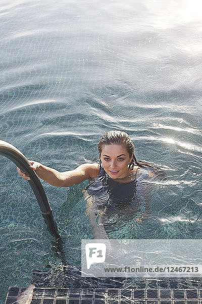Young woman holding railing in swimming pool
