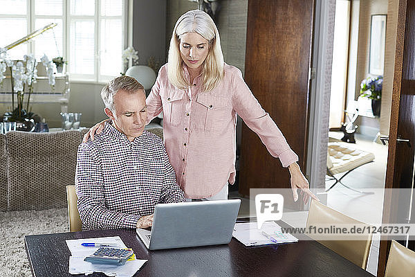 Mature married couple working at home together.