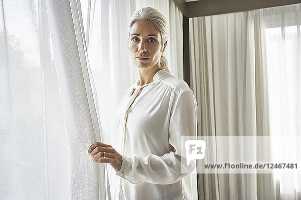 Mature woman standing at window.