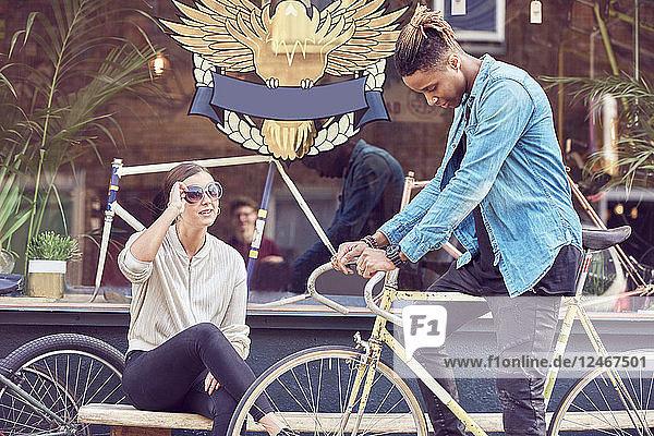 Teenage boy on bicycle talking to his girlfriend