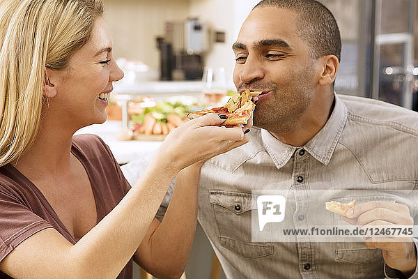 Young woman feeding pizza to her boyfriend