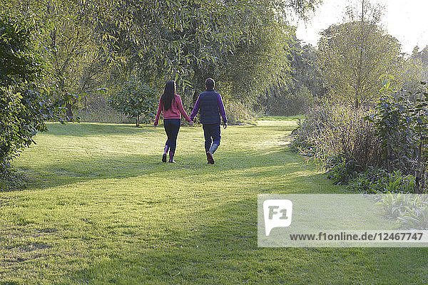 Young couple holding hands while walking through a field.