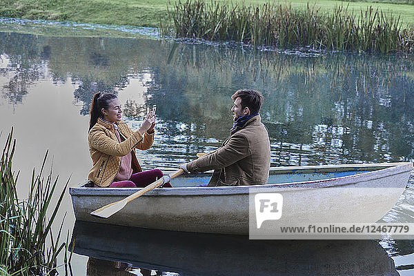 Young woman taking photograph of her boyfriend in rowboat.