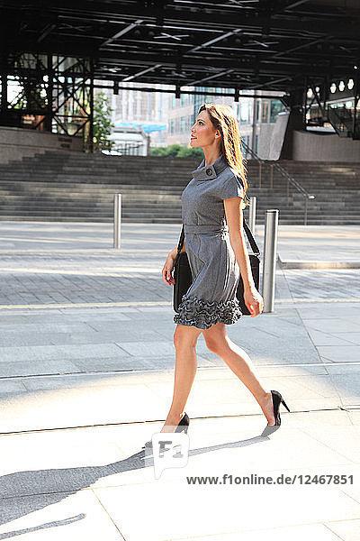 Young woman in gray dress walking