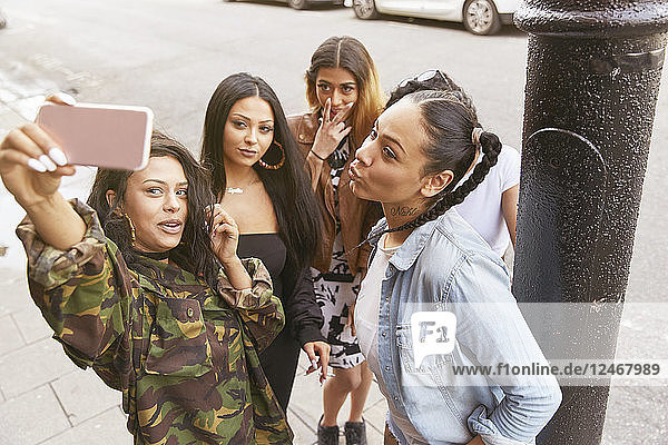 Young woman taking selfie with friends