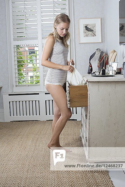 Young woman taking clothes from drawer.