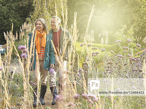 Mature married couple hiking in forest.