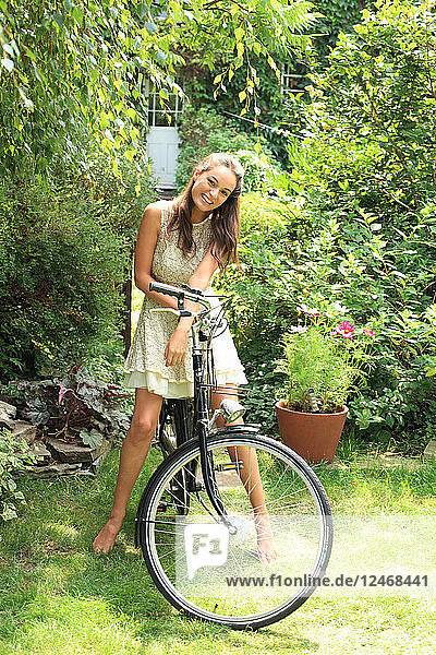 Young woman riding bicycle in garden