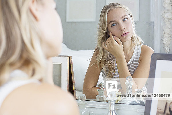 Young woman sitting at dressing table.