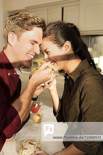 Young couple eating with chop sticks