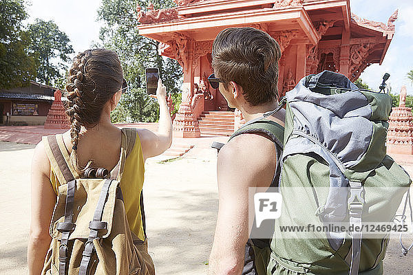 Young couple wearing backpacks at temple