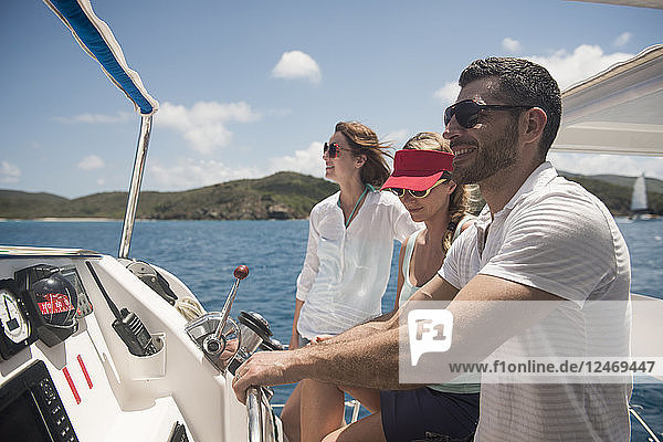 Friends at helm of boat