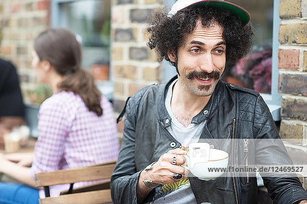 Young man with coffee at outdoor cafe