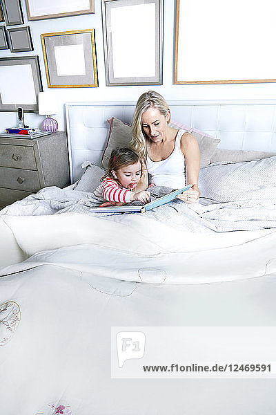 Mother reading book to daughter on bed