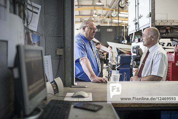 Businessmen talking in repair shop