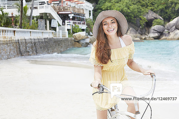 Young woman wearing yellow dress riding bicycle on beach