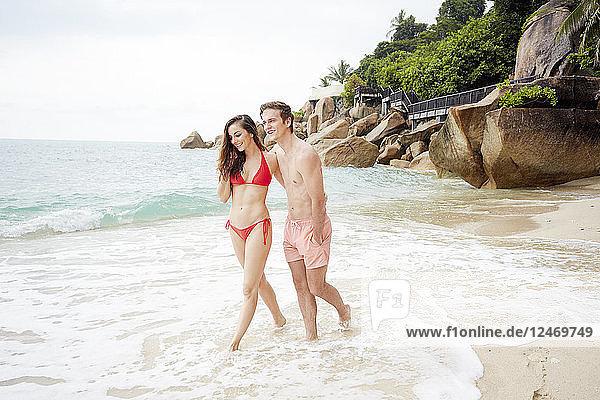 Young couple wearing swimwear walking on beach