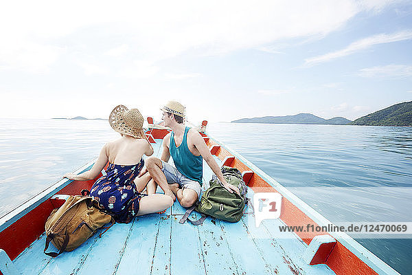 Young couple on boat with backpacks