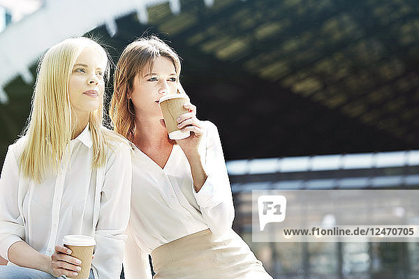 Young businesswomen drinking coffee together.