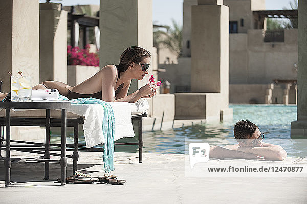 Couple relaxing poolside in Dubai  United Arab Emirates