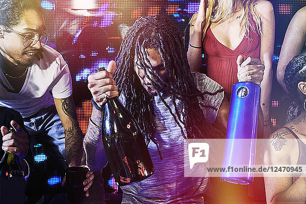 Young man with bottles in nightclub