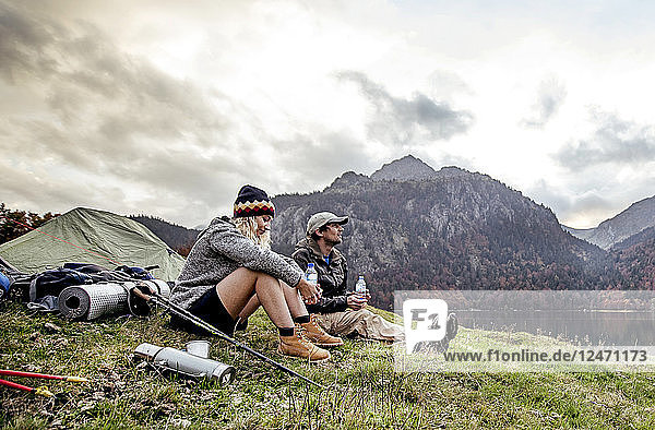 Young couple resting at camp beside mountains