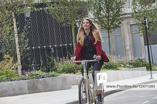 Young woman riding bicycle on city street