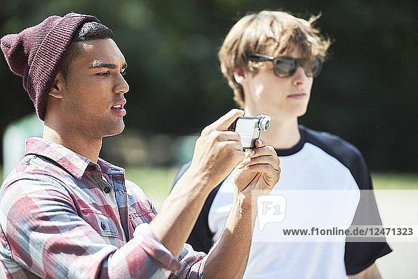 Teenage boy taking photograph with smartphone