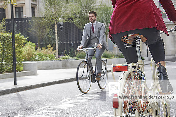 Young man riding bicycle past woman on city street