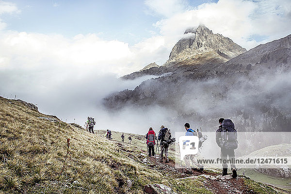 Group of hikers beside foggy mountains
