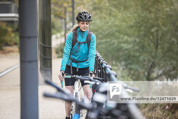 Woman commuting on bicycle beside railing