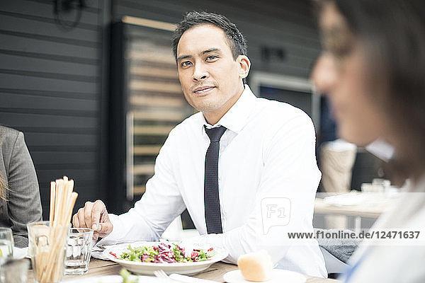 Businessmen shaking hands at restaurant meeting