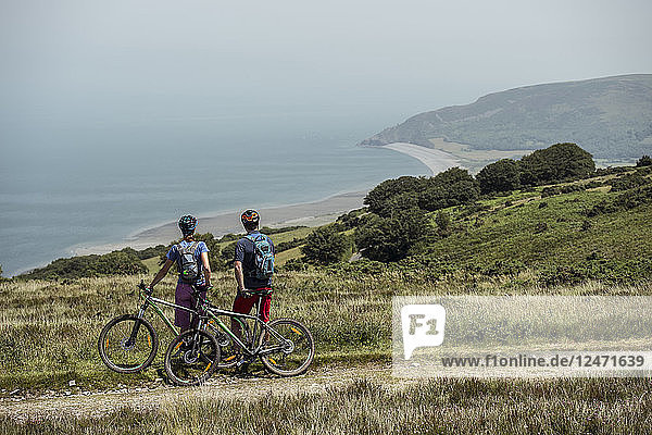 Couple of mountain cyclists on top of hill