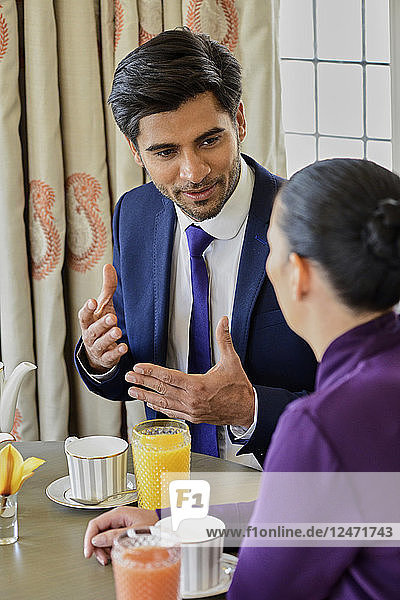 Businessman talking with his colleague at breakfast