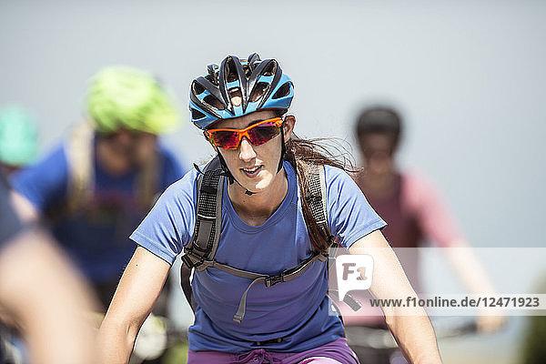 Woman mountain biking with friends in Porlock Weir  England