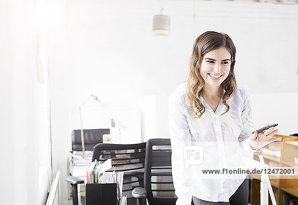 Smiling young businesswoman in office