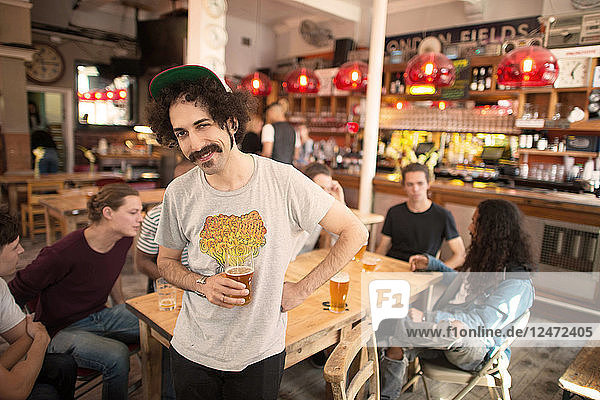 Young man spending time with friends at bar