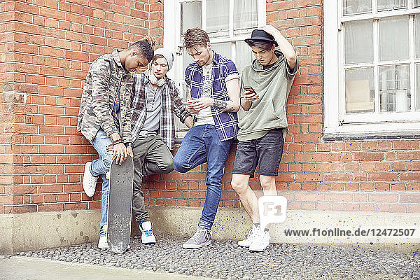Teenage friends leaning against brick wall