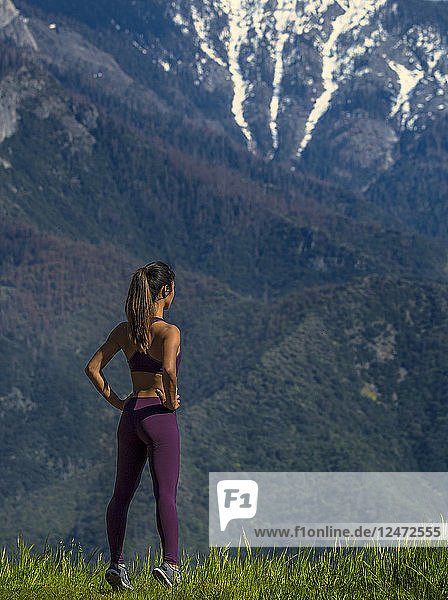 Young woman with hands on hips on a mountain