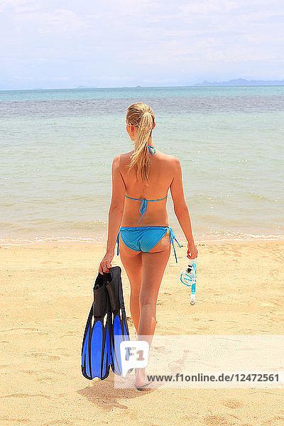 Young woman wearing bikini holding diving flippers on beach