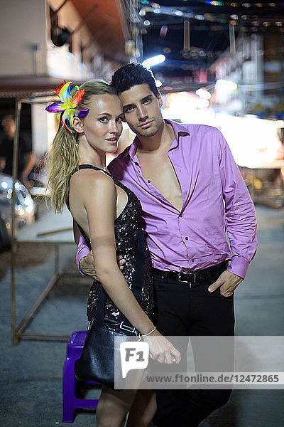 Young couple posing on sidewalk at night