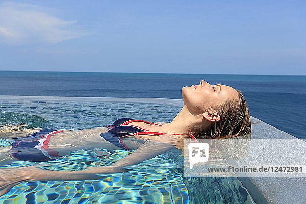 Young woman in swimming pool by sea