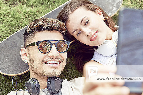 Teenage couple taking selfie and lying on skateboard